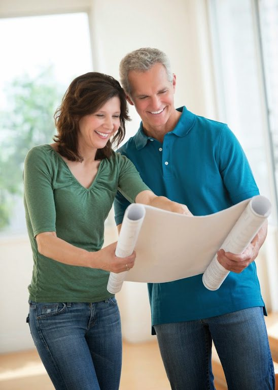 man and woman looking at floor plans